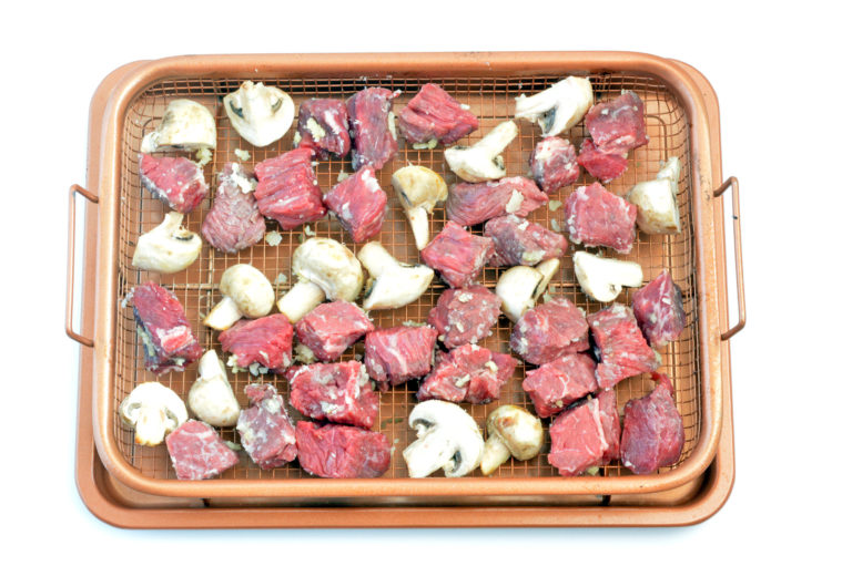 Steak and Mushrooms lined up on an air fryer cookie sheet ready to bake.