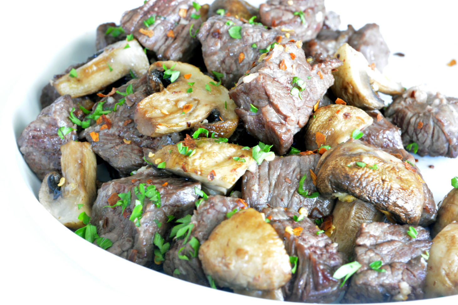 Air Fryer Steak and Mushrooms in a white bowl topped off with parsley.