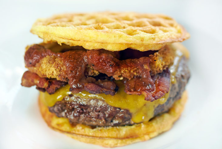 Chaffle loaded with western bacon cheeseburger toppings like onion rings, BBQ sauce and cheese