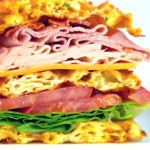 Picture of a Club Sandwich Chaffle cut in half on a white plate. Loaded with turkey, ham, cheese and bacon.
