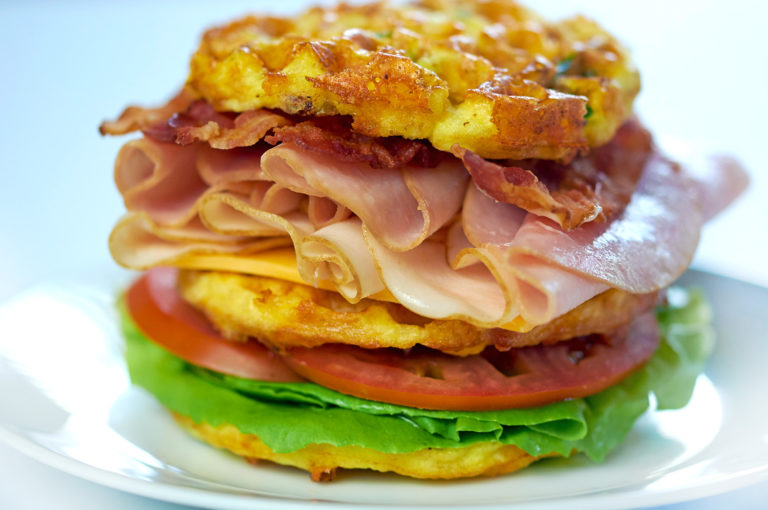 Picture of a Club Sandwich Chaffle on a white plate. Loaded with turkey, ham, cheese and bacon.