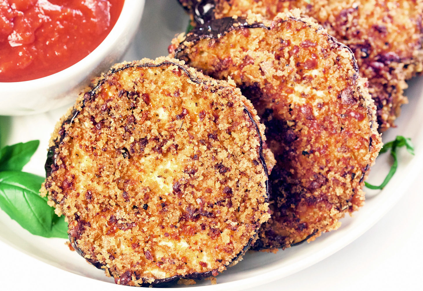 Air Fryer Eggplant Chips being dipped into a bowl of marinara sauce.