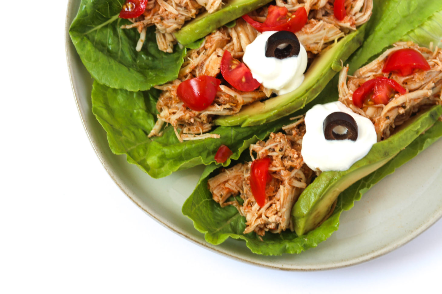 Shredded Chicken in romane lettuce topped with tomatoes, avocado, sour cream, black olives on a white plate