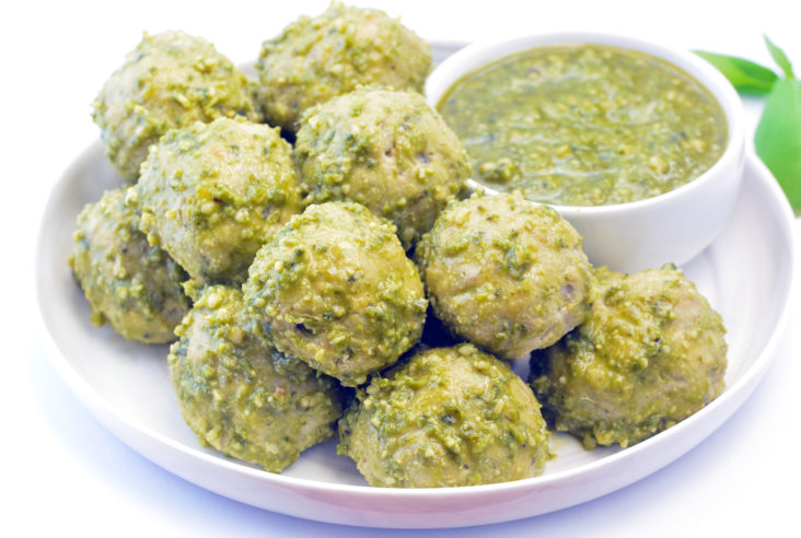 Pesto Meatballs sitting on a white plate with pesto dipping sauce. Made with ground chicken or turkey.