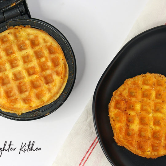 Cooked Chaffles on a Dash Waffle Maker and black plate.