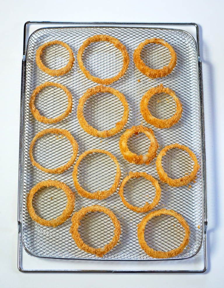 Breaded onion rings on an air fryer baking tray.