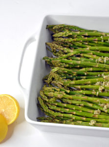 Raw Asparagus with Parmesan and lemon wedge in a white baking dish.