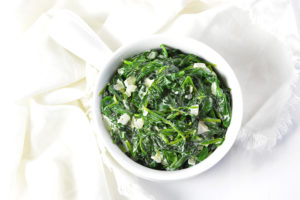 Creamed spinach in a white bowl on a white napkin.