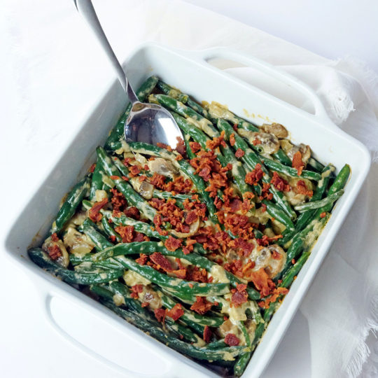 Keto Green Bean Casserole with bacon crumbles and mushrooms in a white baking dish.
