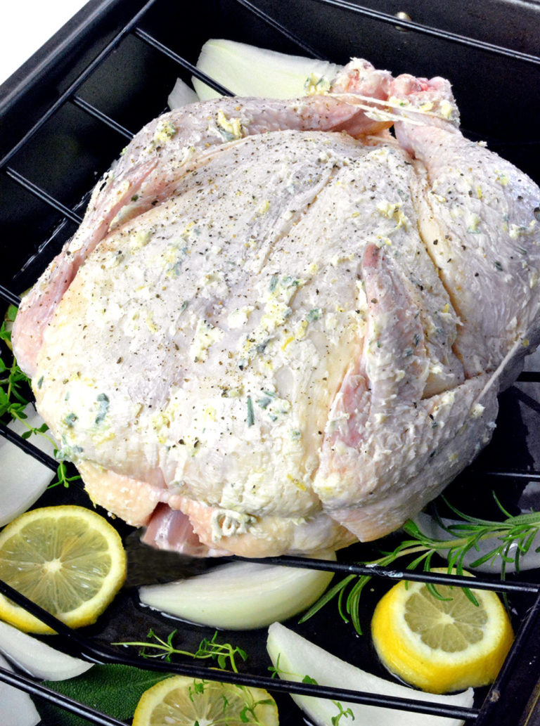 Raw whole chicken in a black roasting pan surrounded by lemon, onion and herbs.