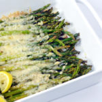 Baked Asparagus with Parmesan and lemon wedge in a white baking dish.