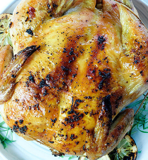 Whole chicken on a white plate surrounded by lemon, onion and herbs.