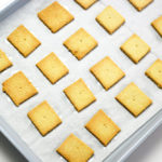 Baked Keto Crackers on parchment paper lined silver baking sheet.