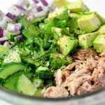 Clear glass bowl containing ingredients for tuna with avocado salad: tuna, cucumber, avocado, onions and cilantro